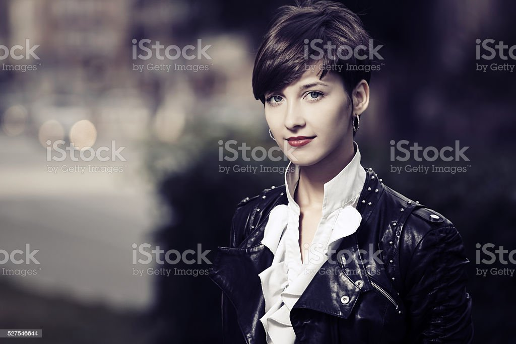 Happy young fashion woman in leather jacket outdoor stock photo