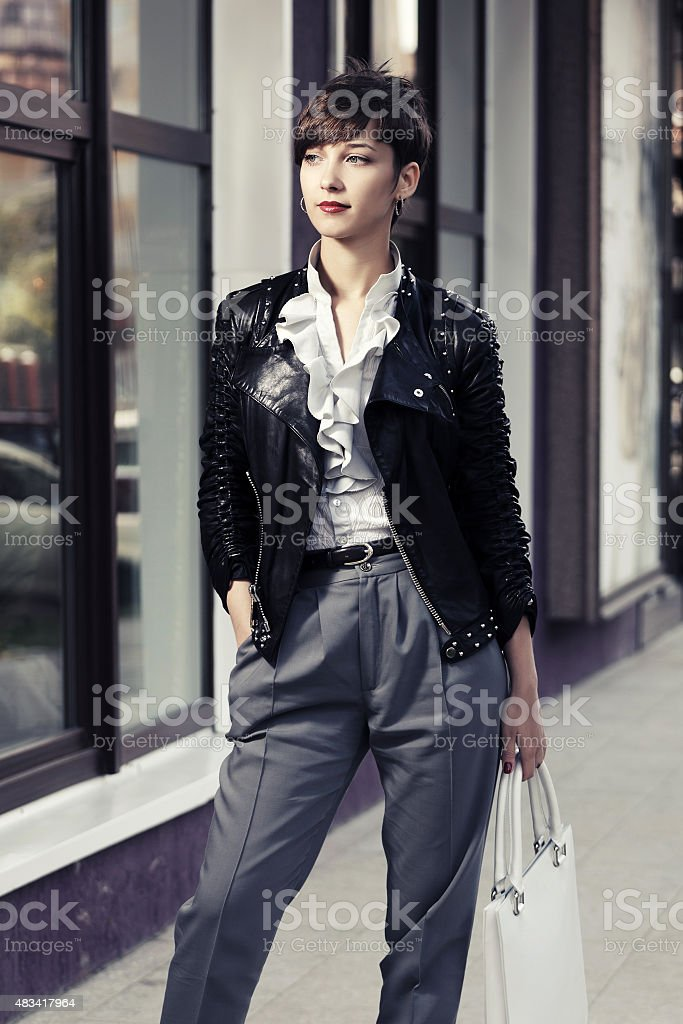 Happy young fashion woman in leather jacket with handbag stock photo