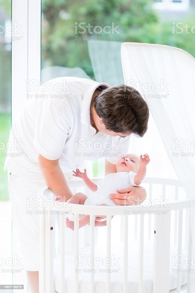 Happy young father holding newborn baby in crib near window royalty-free stock photo