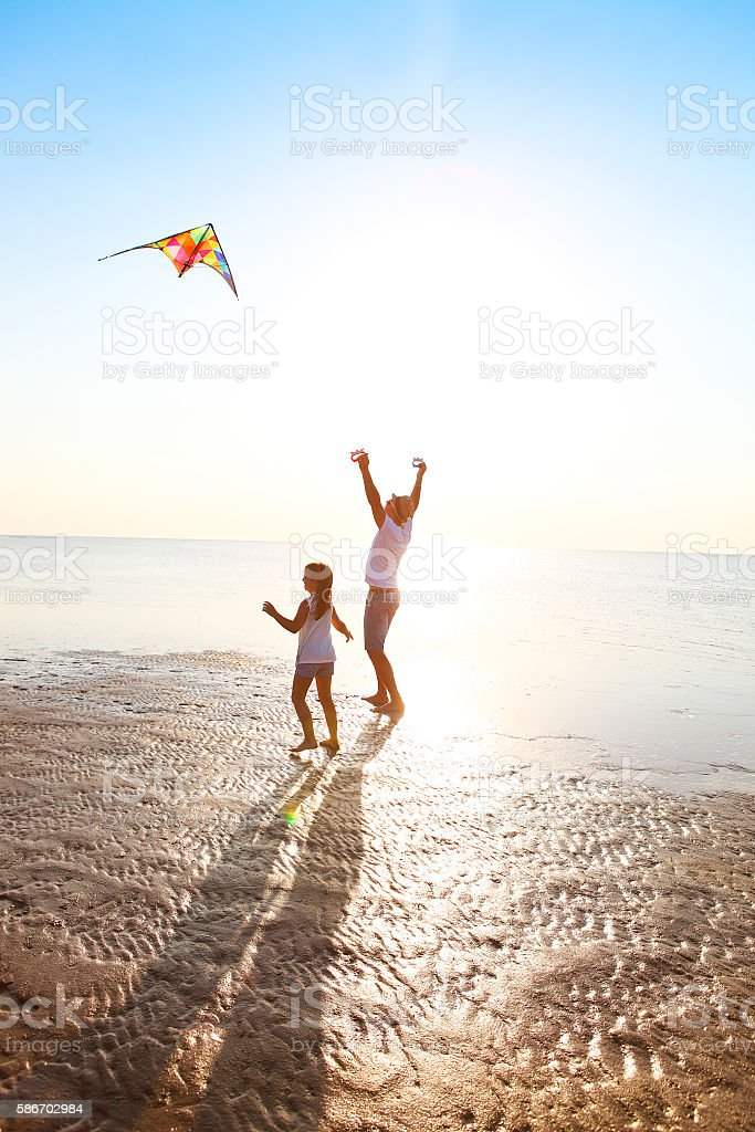 Happy young father with daughter and flying kite on beach stock photo