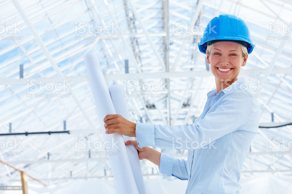 Happy young female architect holding blueprint at construction site royalty-free stock photo