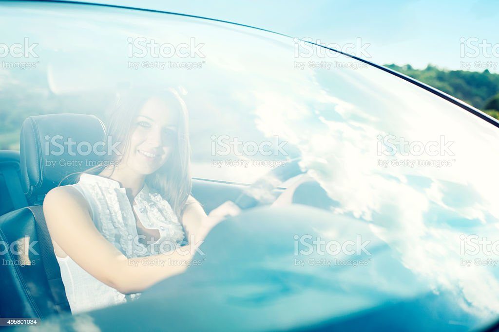 Happy young female driving car stock photo