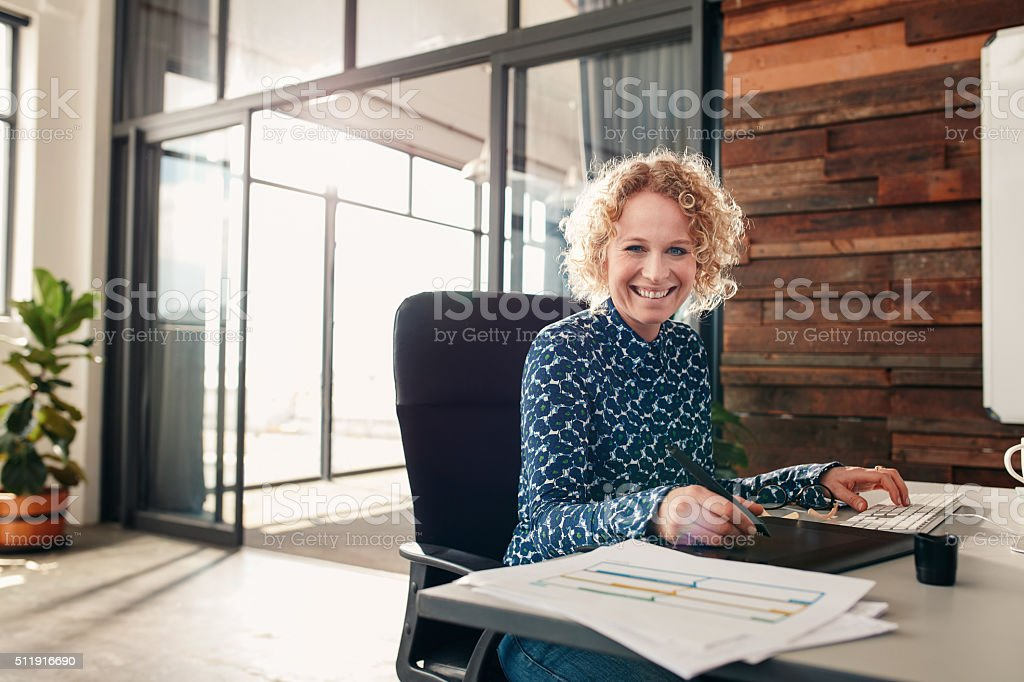 Happy young female graphic designer working at her desk stock photo