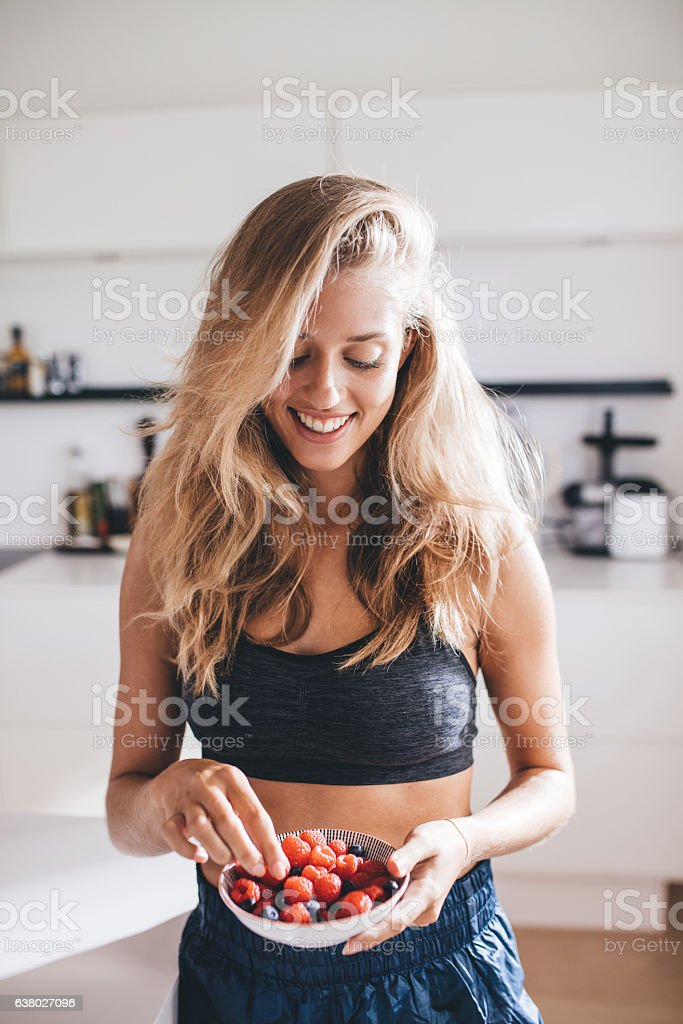 Happy young female in kitchen eating berries stock photo