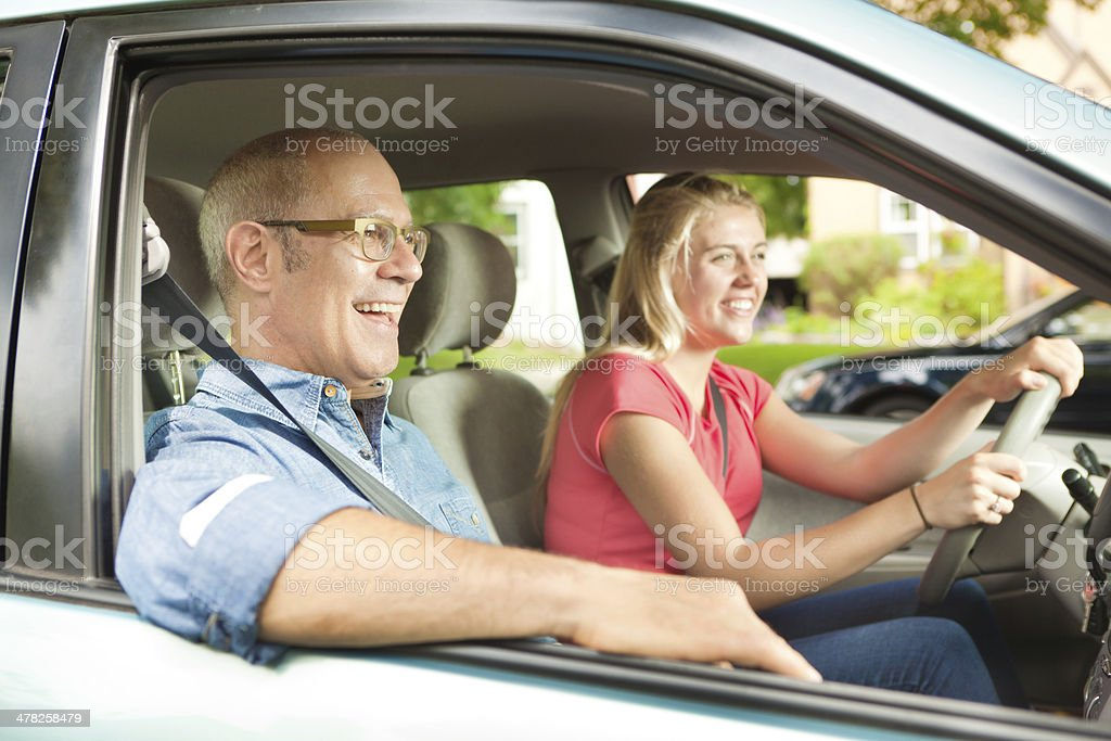 Happy Young Female Teenager Driver Driving with Parent or Instructor stock photo
