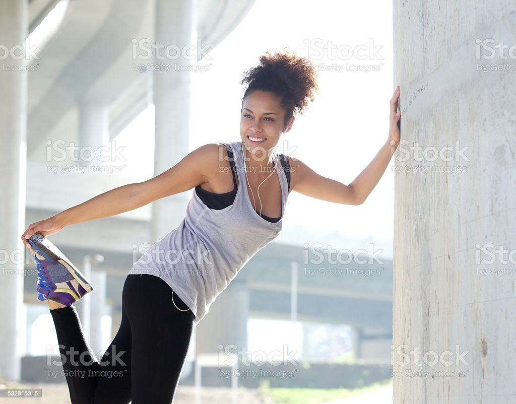 Happy young fitness woman stretching outdoors stock photo