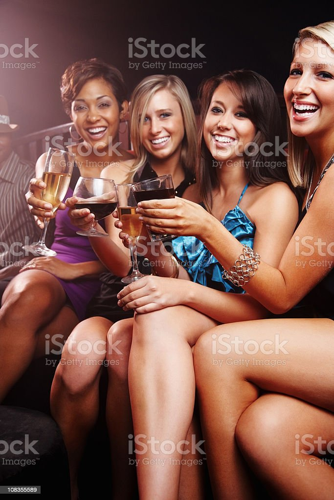 Happy, young friends enjoying at a party with drinks royalty-free stock photo