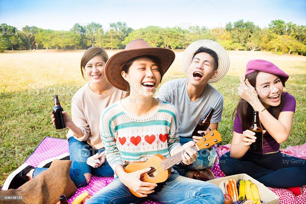 happy young friends enjoying picnic and playing ukulele stock photo