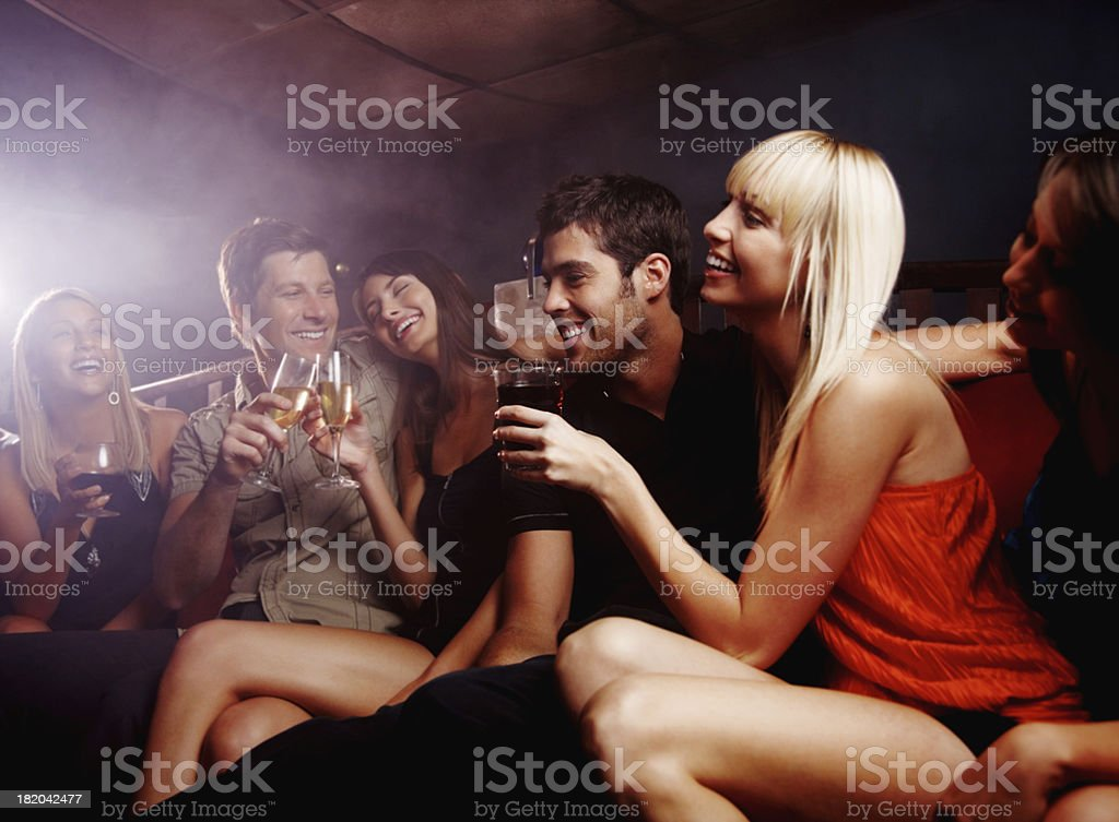 Happy, young friends enjoying their drinks at a night club stock photo