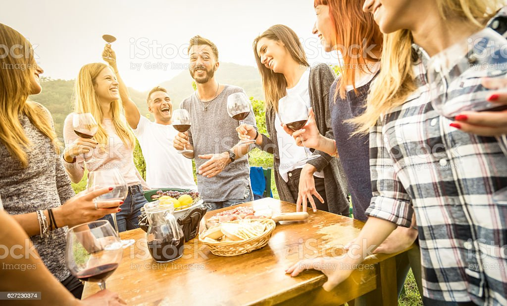 Happy young friends having fun outdoor drinking red wine stock photo