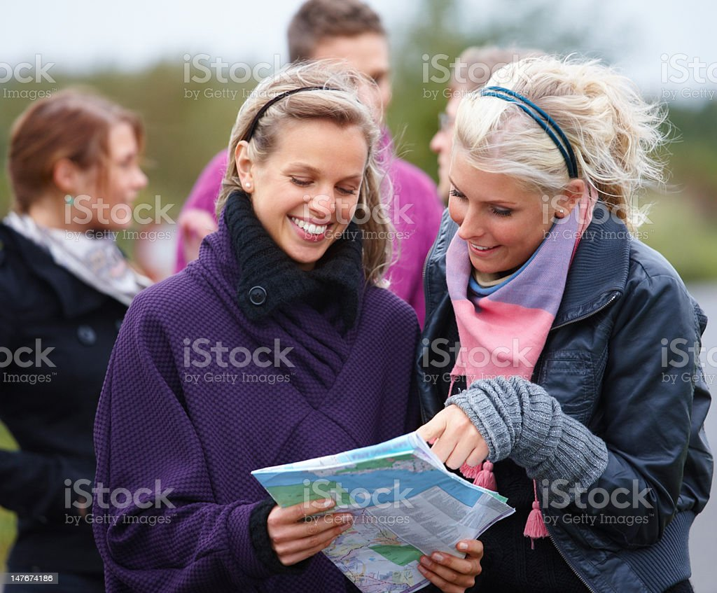 Happy young friends looking at map royalty-free stock photo