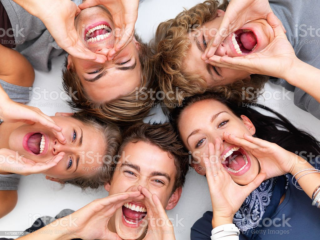Happy young friends lying together and shouting royalty-free stock photo