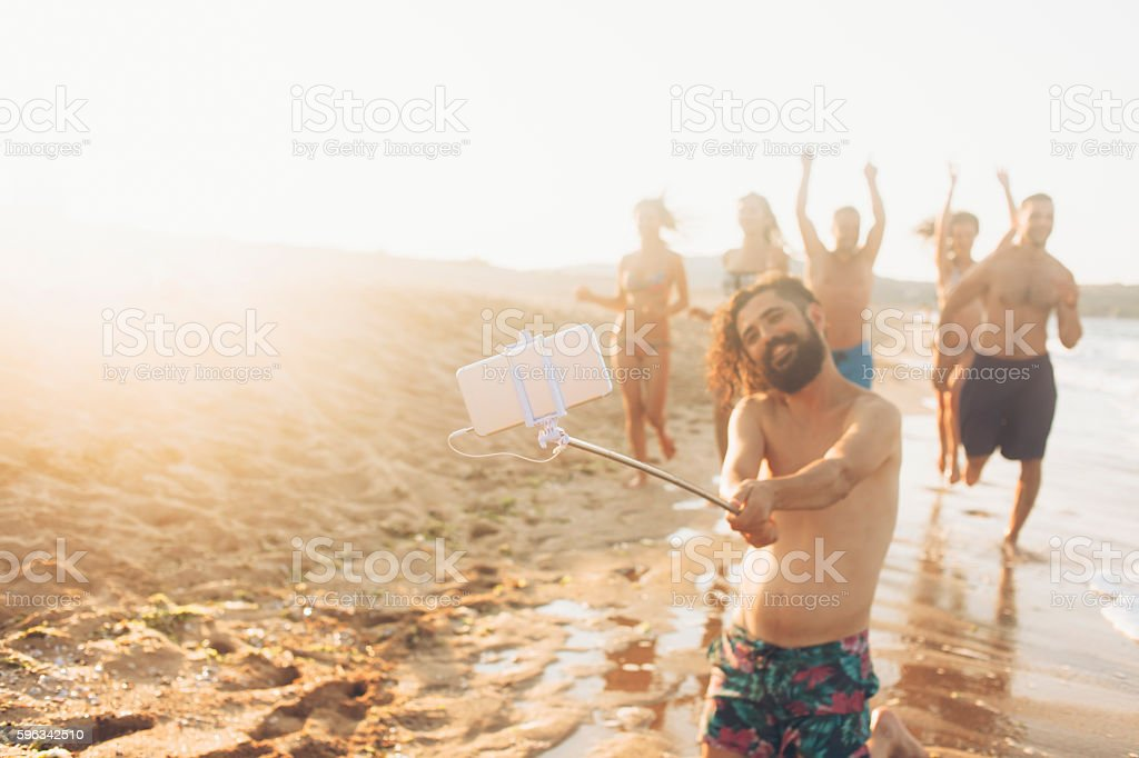 Happy young friends making selfie on the beach stock photo