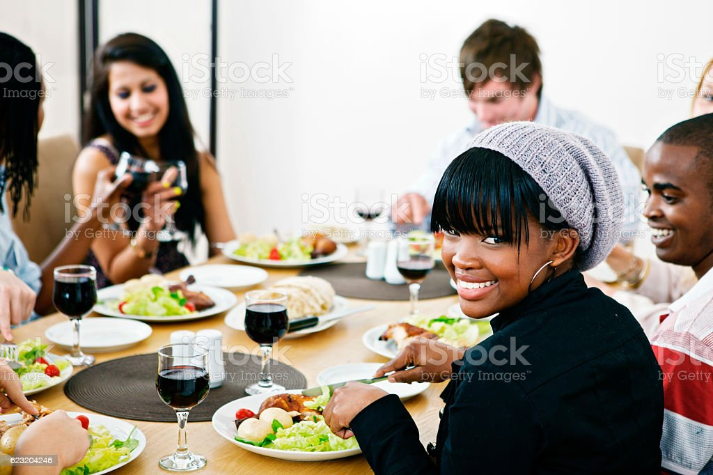 Happy young friends or co-workers enjoying a meal together stock photo
