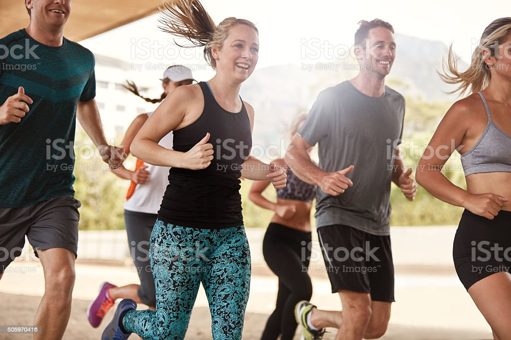Happy young friends running together stock photo
