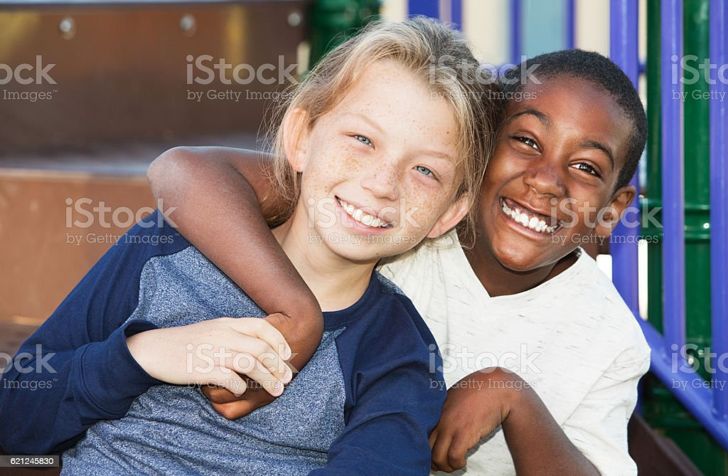 Happy young friends sitting together stock photo