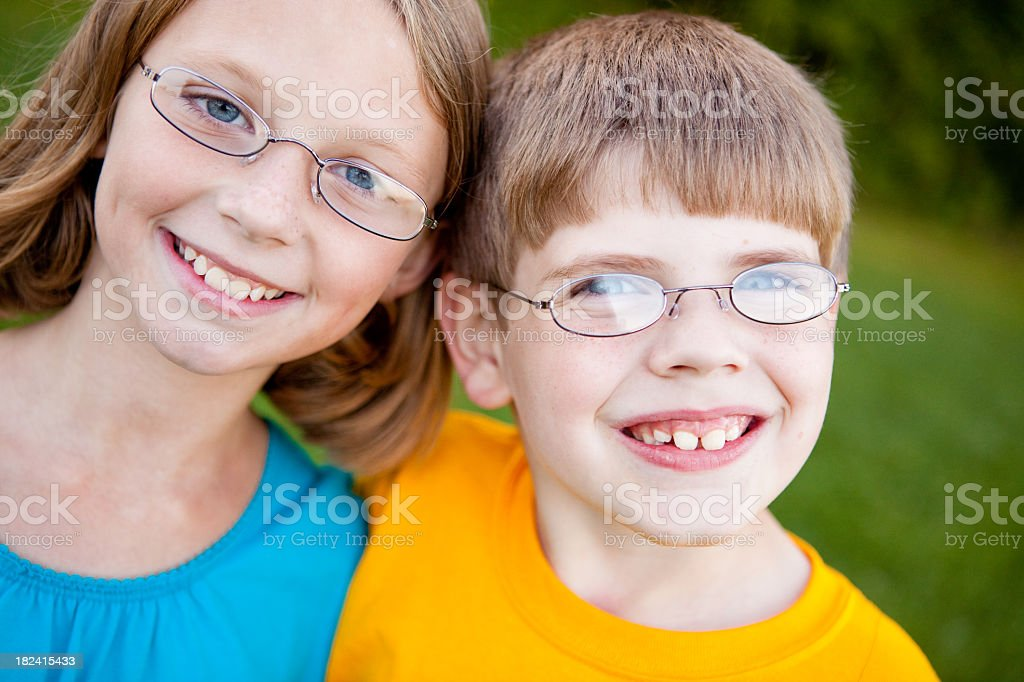 Happy Young Girl and Boy with Glasses Smiling Outside royalty-free stock photo