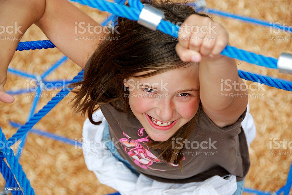 A happy young girl climbing at the park royalty-free stock photo