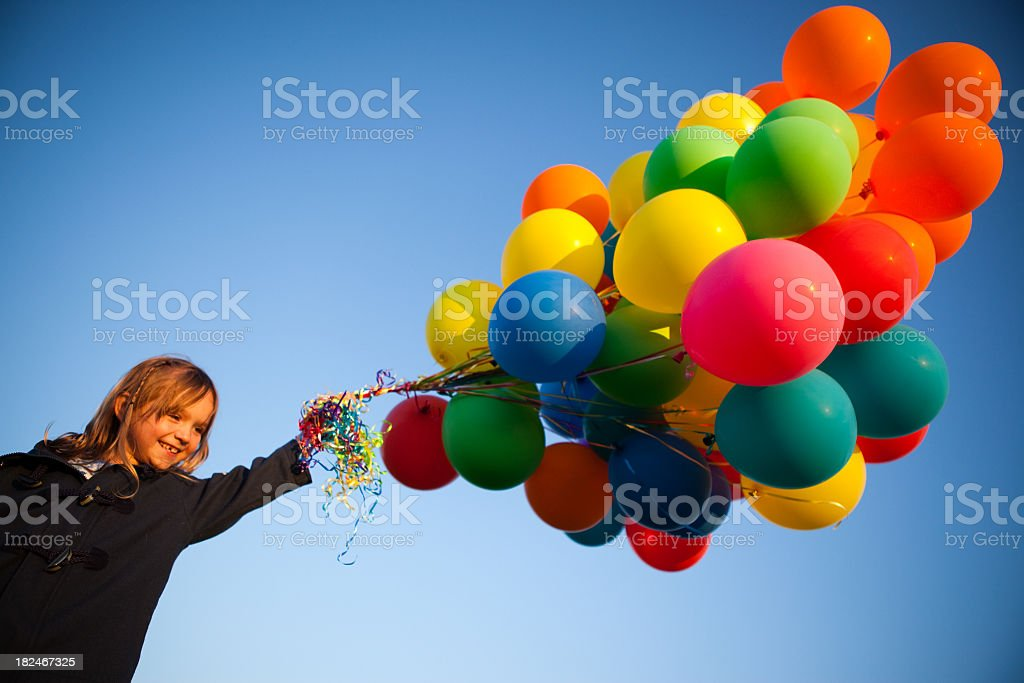 Happy Young Girl Holding a Bunch of Balloons Outside royalty-free stock photo