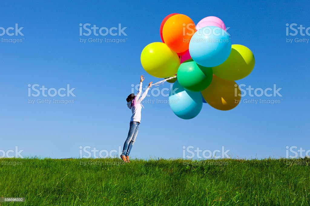 Happy Young Girl Holding a Bunch of Balloons stock photo