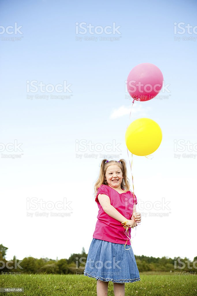 Happy Young Girl Holding Balloons Outside royalty-free stock photo