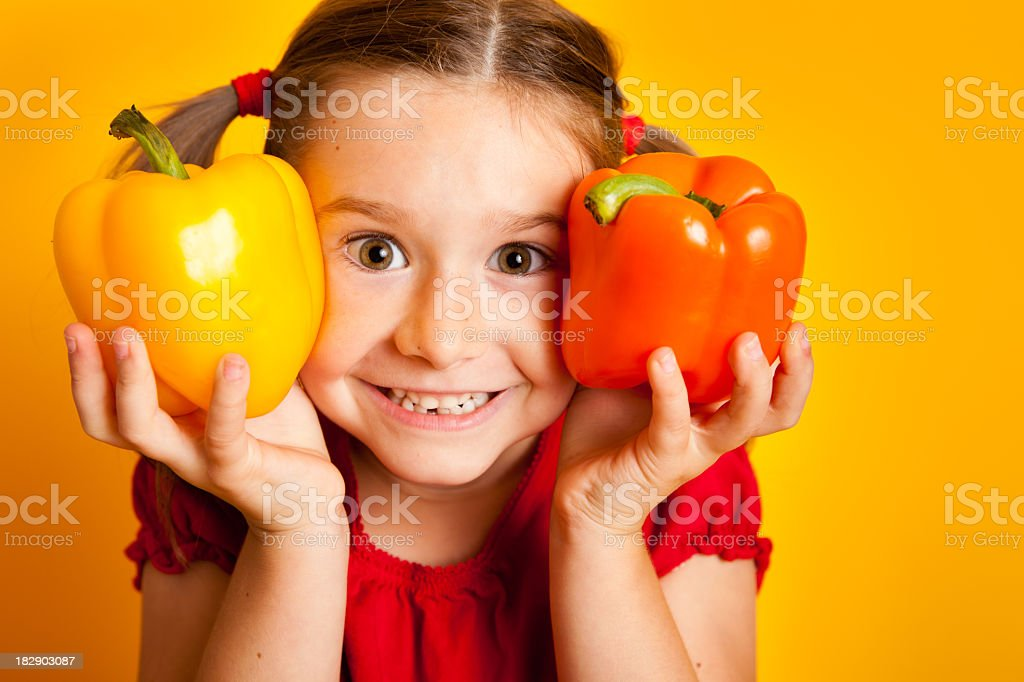 Happy Young Girl Holding Yellow and Orange Bell Peppers royalty-free stock photo