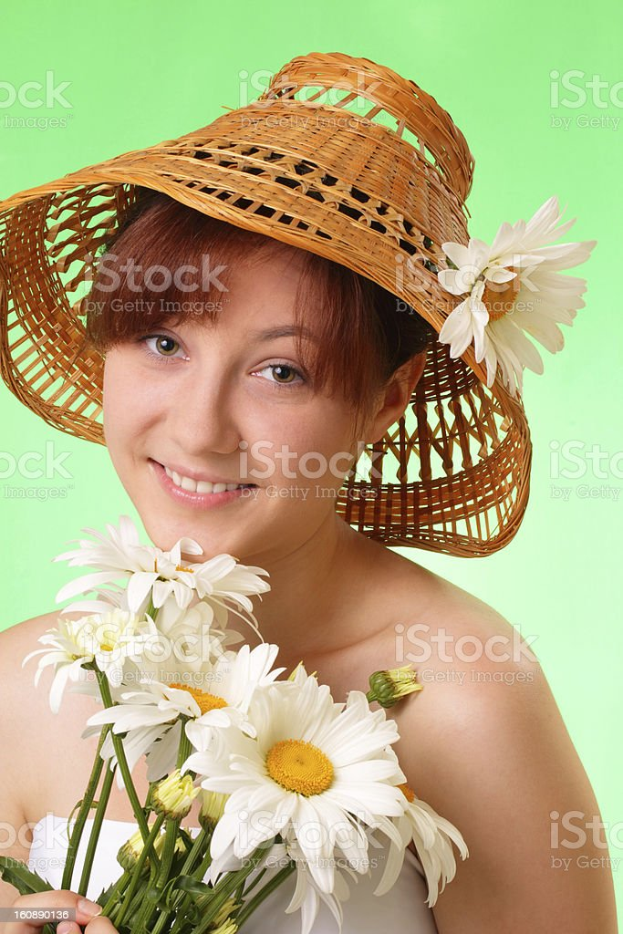 Happy young girl in the hat with chamomile flowers royalty-free stock photo