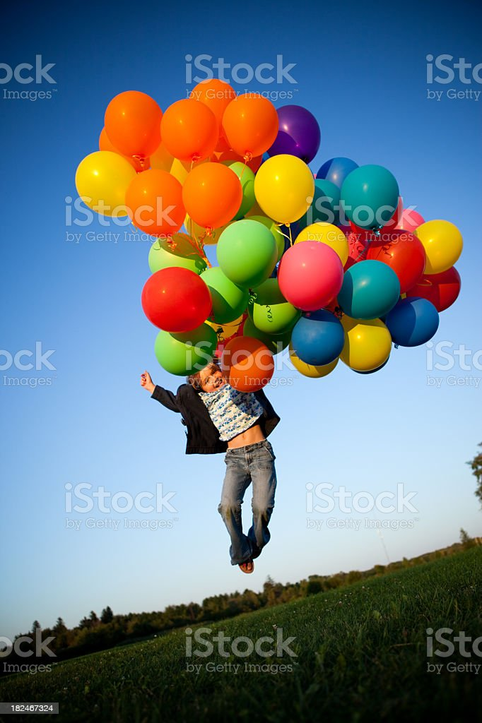 Happy Young Girl Jumping with a Bunch of Balloons Outside royalty-free stock photo