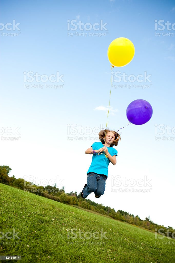 Happy Young Girl Jumping with Balloons Outside royalty-free stock photo