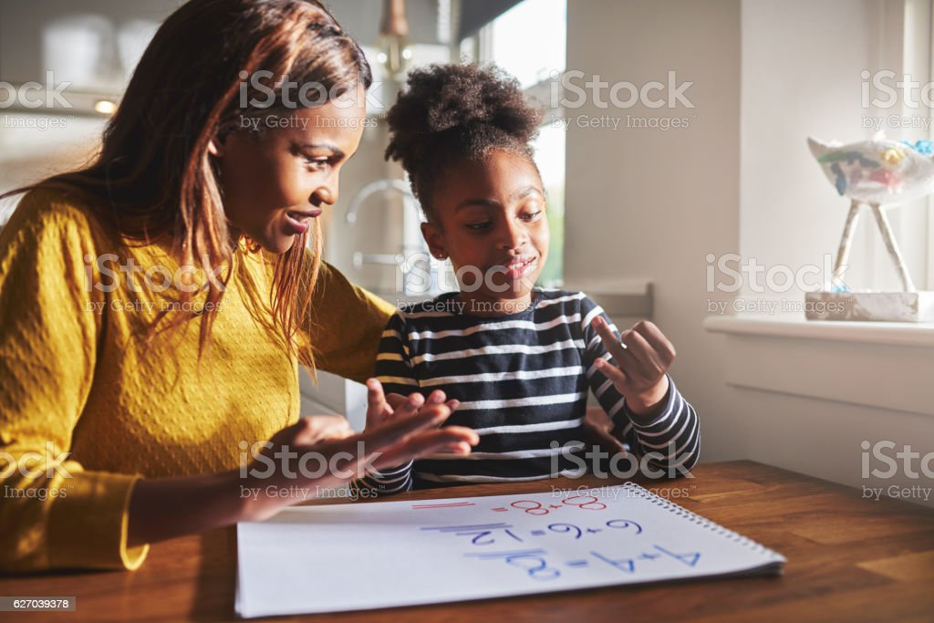 Happy young girl learning to calculate stock photo