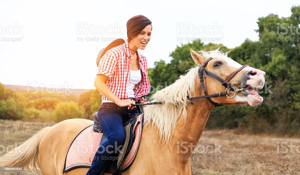 Happy young girl riding horse stock photo