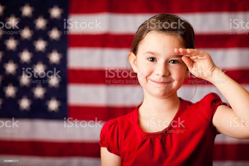 Happy, Young Girl Smiling and Saluting by American Flag stock photo