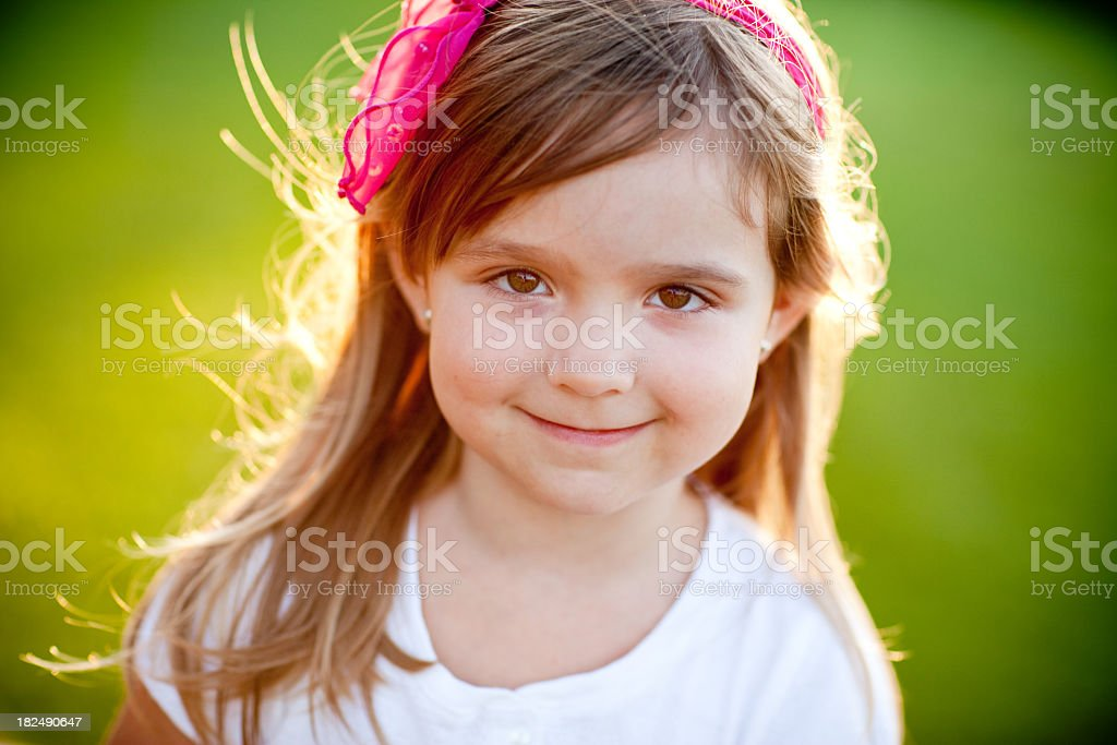 Happy Young Girl Smiling while Backlit by Evening Sun royalty-free stock photo