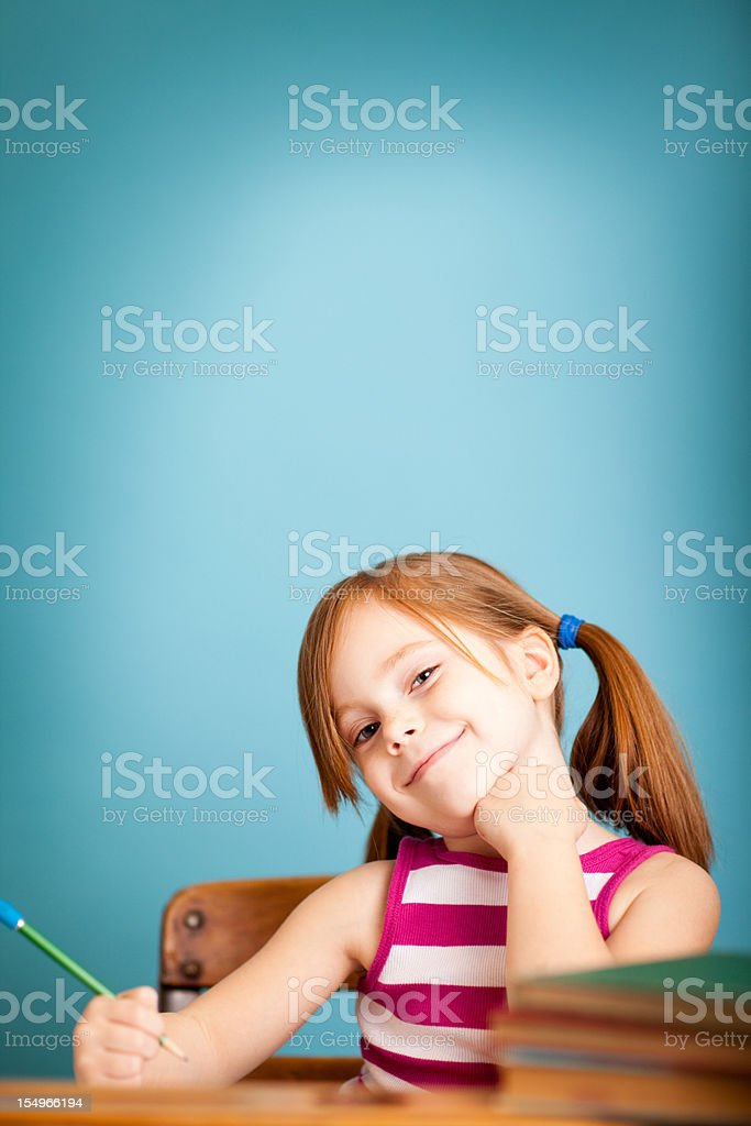 Happy, Young Girl Student Sitting in School Desk royalty-free stock photo