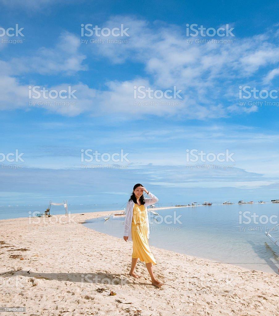 happy young girl walks on long narrow beach royalty-free stock photo