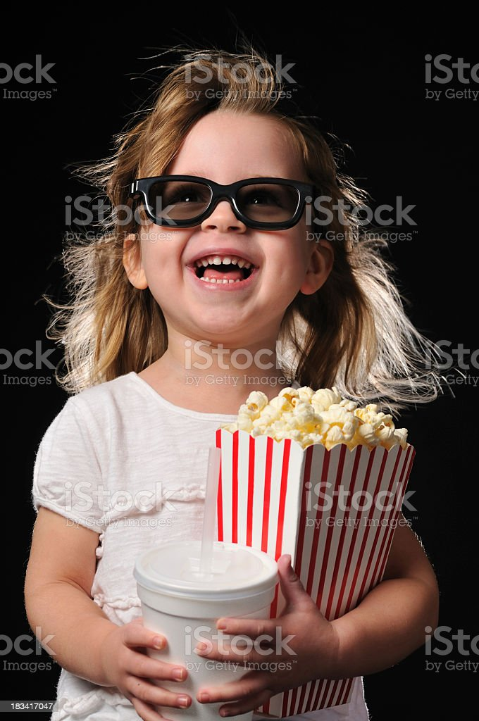Happy young girl with a drink and popcorn wearing 3D glasses royalty-free stock photo