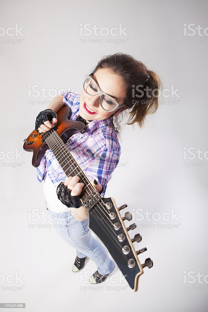 Happy young girl with glasses playing on electric guitar royalty-free stock photo