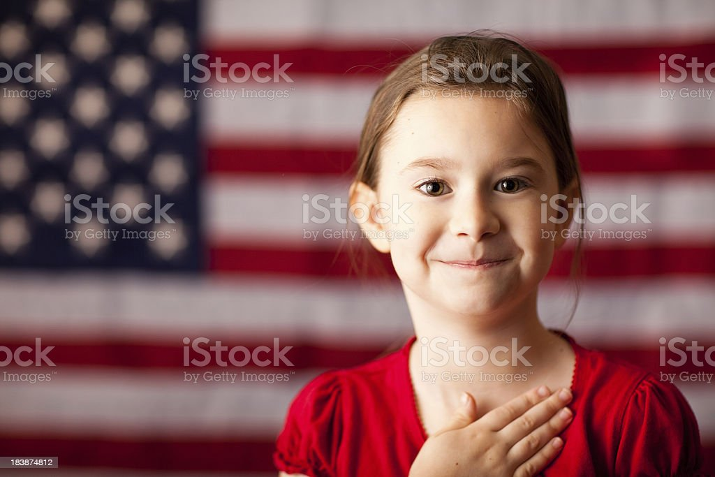 Happy Young Girl with Hand on Heart by American Flag stock photo