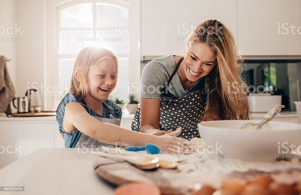Happy young girl with her mother making dough stock photo