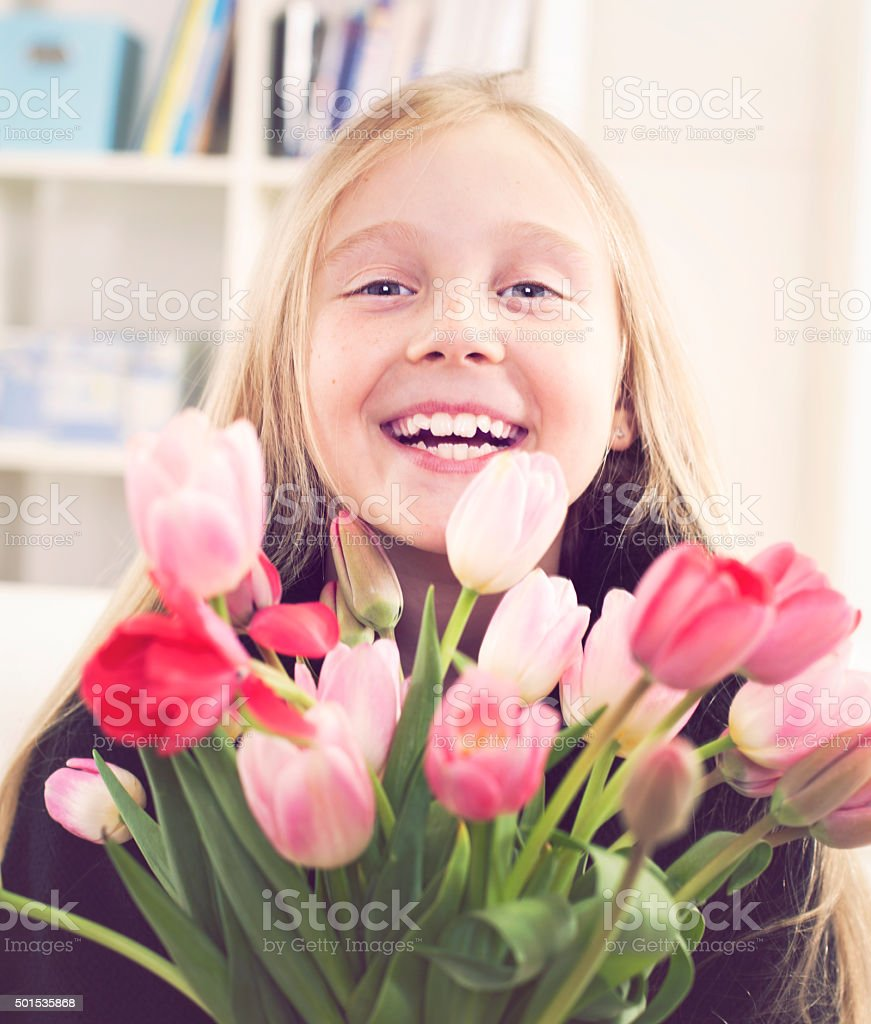 Happy young girl with tulips bouquet stock photo