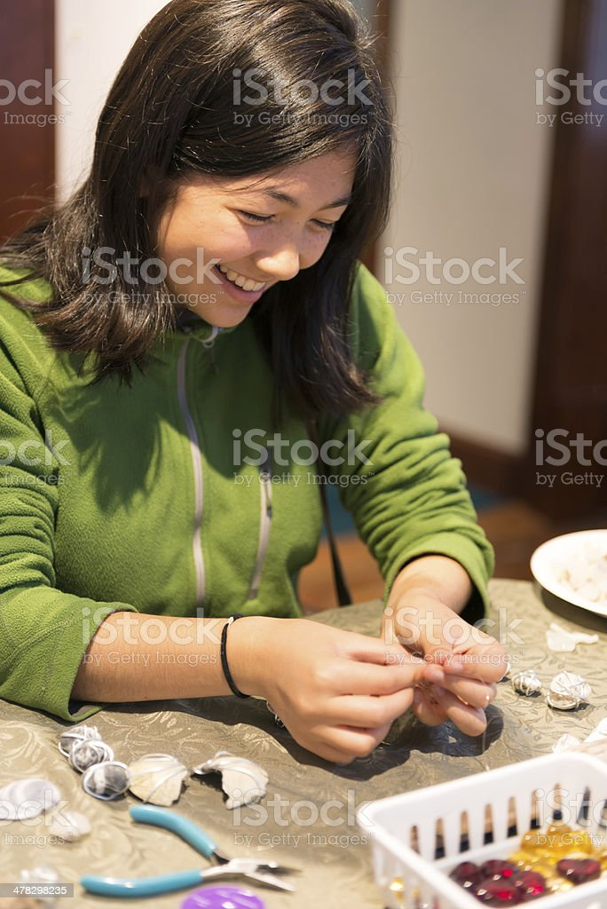 Happy Young Girl Working on Sea Shell Craft Project royalty-free stock photo