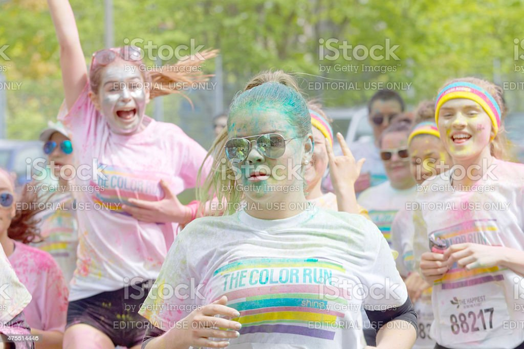 Happy young girls covered with color powder running stock photo