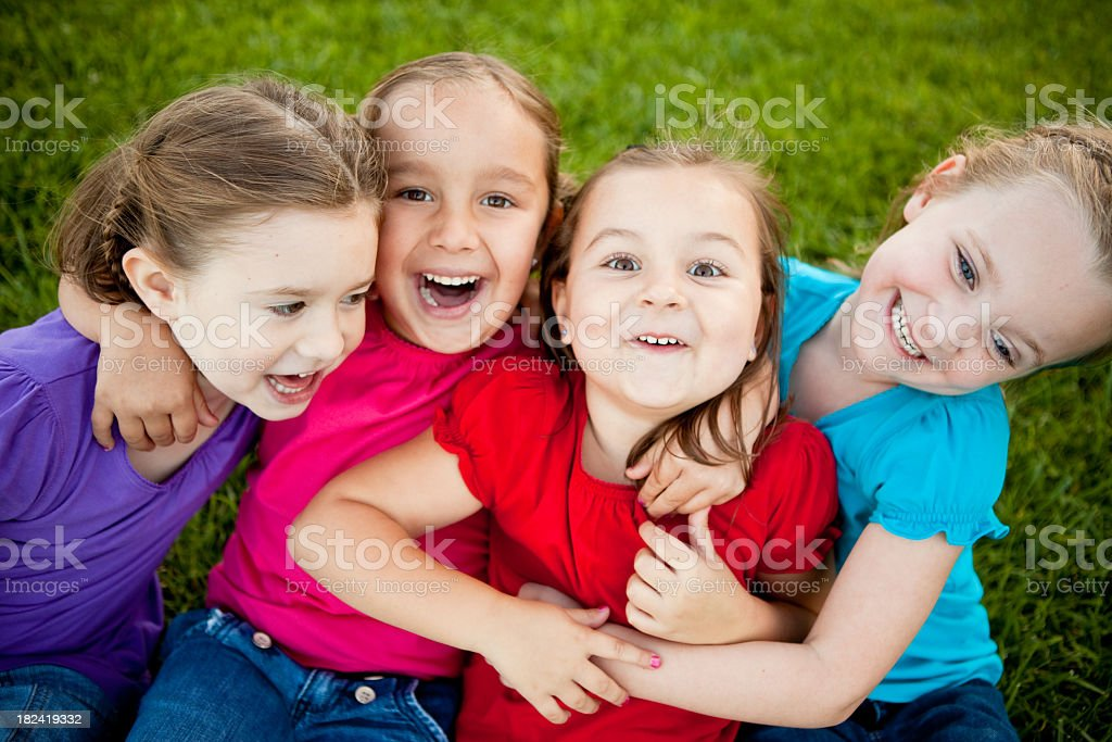 Happy Young Girls Hugging and Laughing Together Outside royalty-free stock photo
