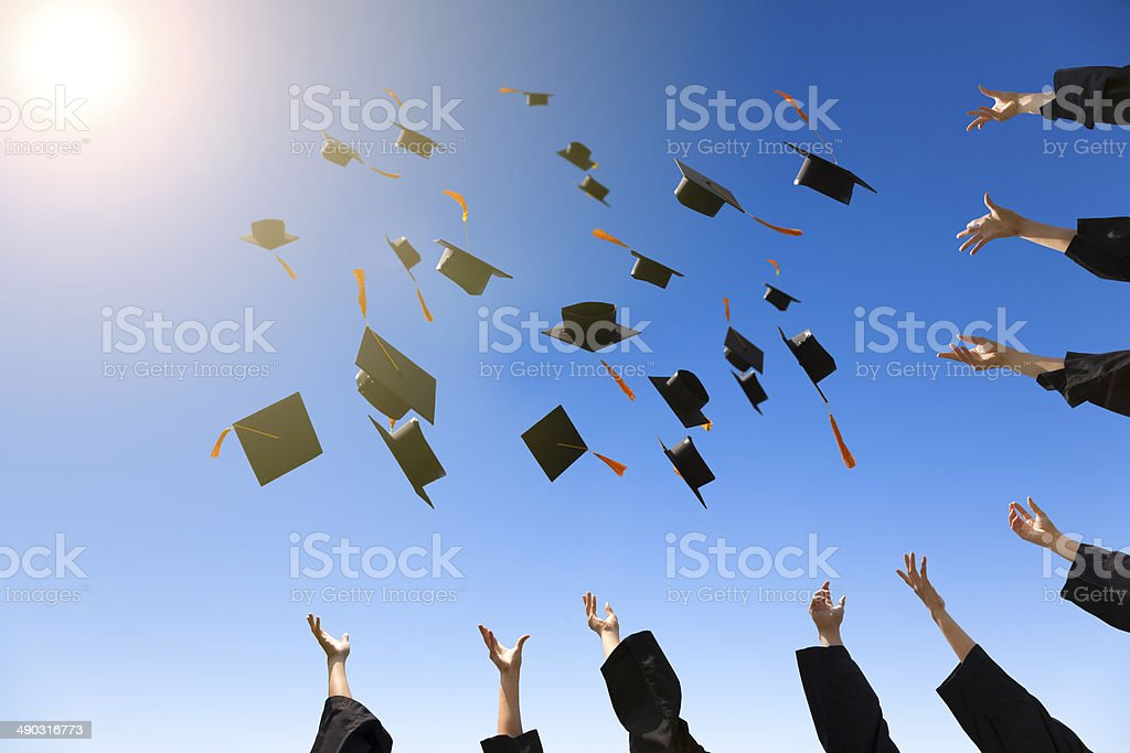 happy young graduates throwing hats stock photo
