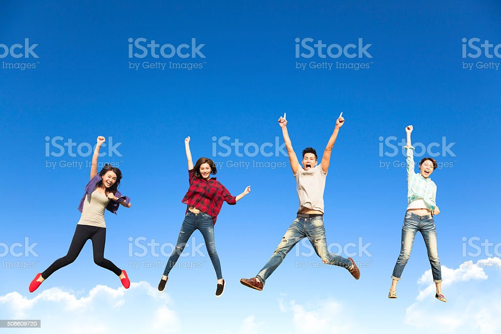 happy young group jumping together stock photo