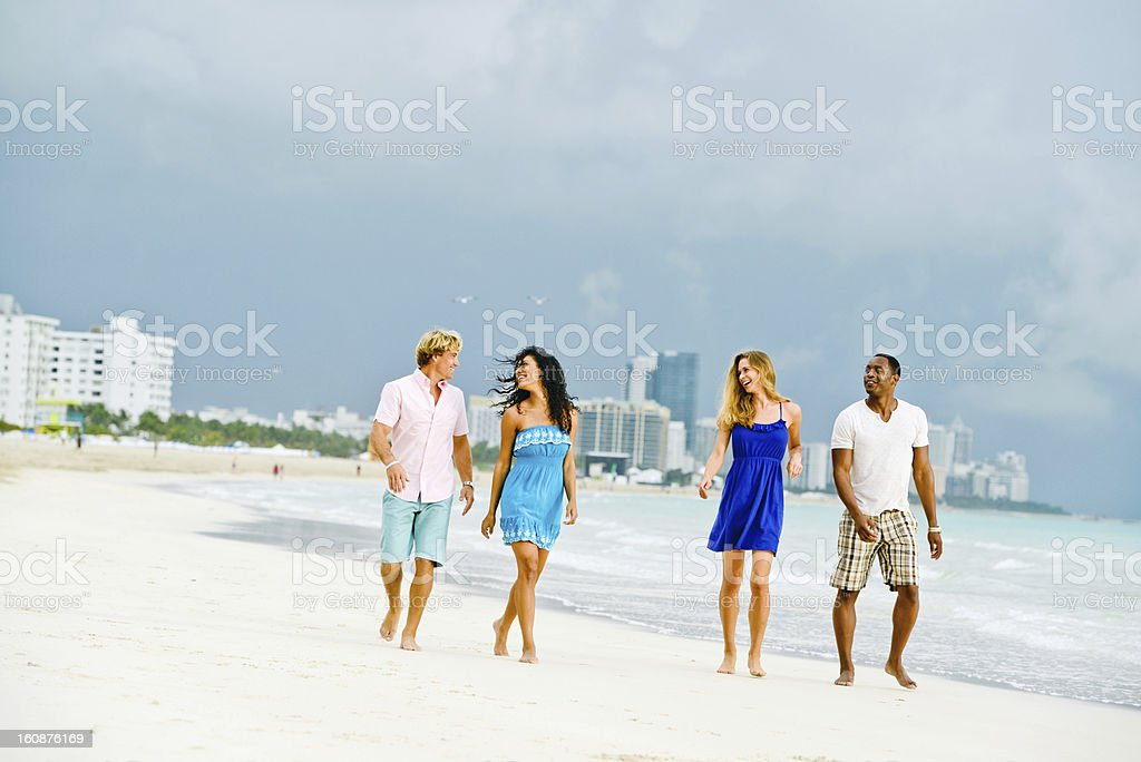 Happy Young Group of Friends Walking on the Beach royalty-free stock photo