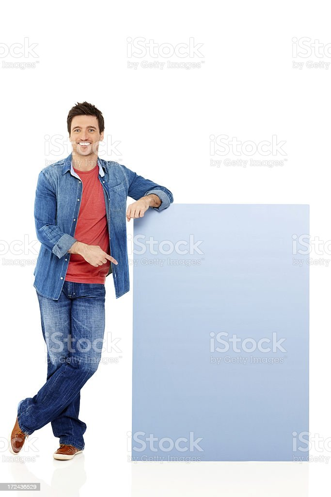 Happy young guy pointing at empty copyspace over white royalty-free stock photo
