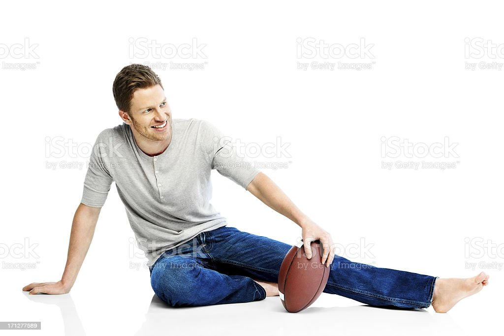 Happy young guy with American football looking away royalty-free stock photo