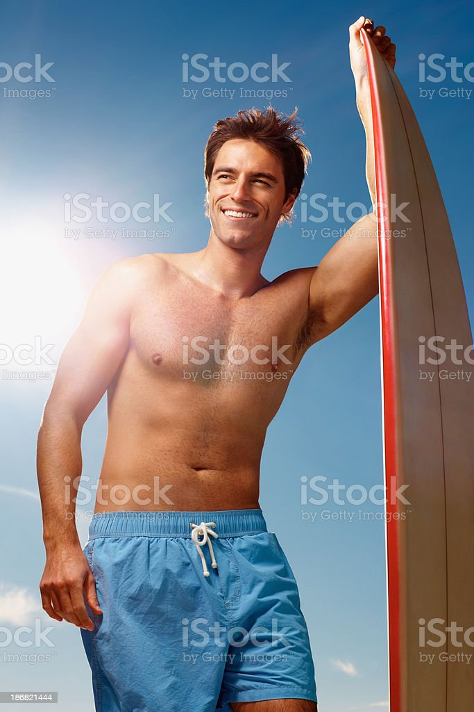 Happy young guy with surfboard against the clear blue sky royalty-free stock photo