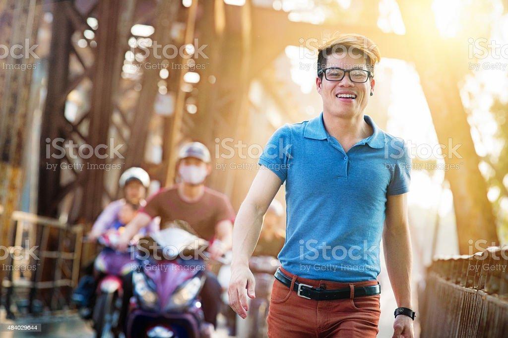 Happy young hip Vietnamese man crossing Long Bien bridge Hanoi stock photo